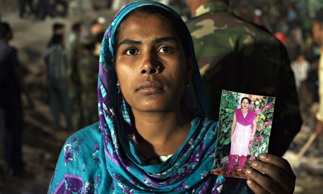 A woman holding a picture of her missing relative at the collapse site of the Rana Plaza factory. Photograph: BBC/Quicksilver Media/Taslima Akhter