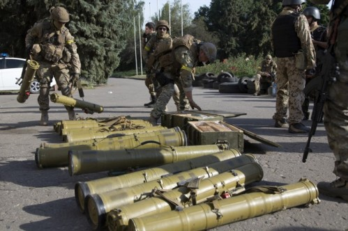 Ukrainian government army soldiers examine weapons captured from rebels in the city of Slovyansk, Donetsk Region, eastern Ukraine on July 5, 2014 (For source of image see link)