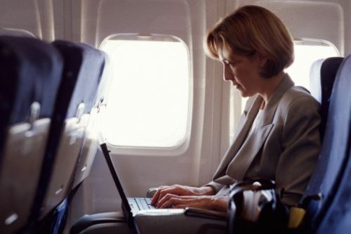 woman on plane with laptop