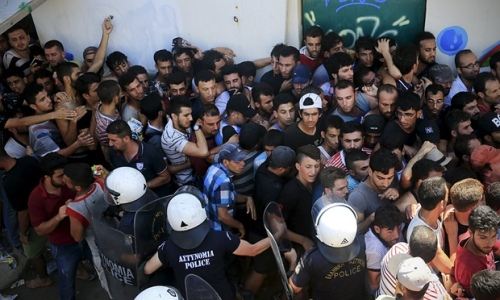 Migrants and refugees are hemmed in by riot police at a stadium on Kos on 12 August. Photograph: Alkis Konstantinidis/Reuters