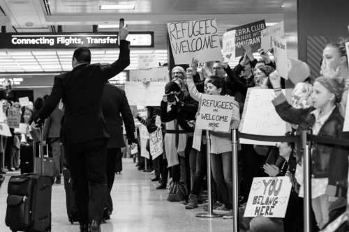 """Refugees Welcome."" Photo from Dulles International Airport in Virginia, capturing crowds protesting the Trump administration's executive order on immigration. Photo by Geoff Livingston. CC BY-NC-ND"